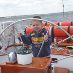 Captain Corbin steering the Schooner Woodwind