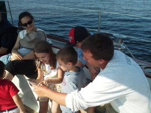 Frank reading to the kids aboard Woodwind about the different sailboats on the Bay.