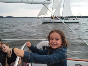 "Millie sailing Woodwind II while ""racing"" Woodwind back into the harbor."