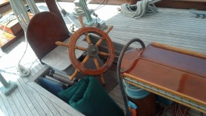 The helm.  The wheel faces aft because it is geared directly to the rudder.  You stand to one side to steer.  This is very reliable and not uncommon.