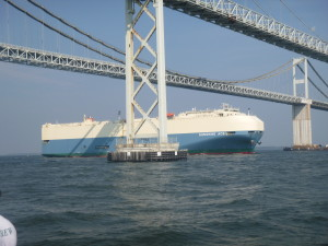Car carrier going under the bridge.
