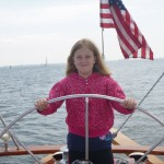 Erinn at the helm of the Schooner Woodwind