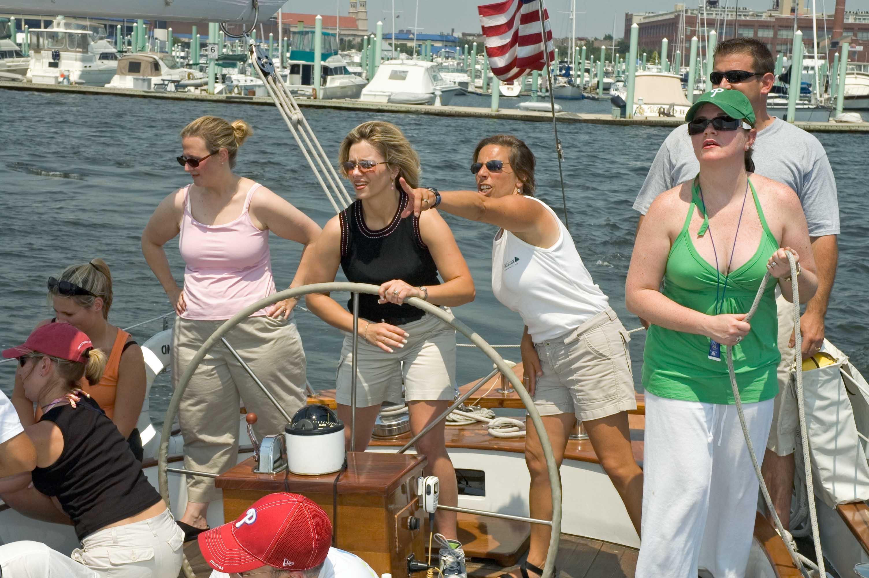 Team Building guests steering with captain pointing out marks