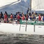 Children waving from the schooner that is breezing along