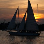 Schooner silhouetted by sunset and water