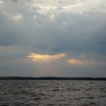 Rays of sun peaking through clouds over the water
