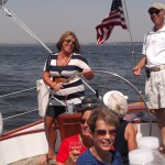 Women in stripped dress at the helm with Captain Ken