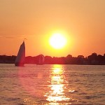 Bright ball of sun and sail boats