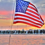 American flag from the Schooner with sunset and Naval Academy behind it