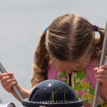 Little girl in pink vest with her head down for a picture at the helm