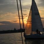 Sun shining through a sailboat sails
