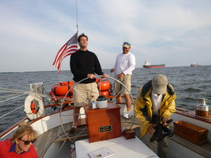 Andy checks main trim as our guest takes the helm.