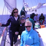 Guests smiling and enjoying beverages and a great cruise on the schooner