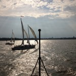 The sun shining on the schooner and the water and creating a shadow of the schooner