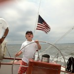 Young boy steering the schooner with a breeze blowing the American Flag