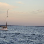 Sailboat moored on blue waters with a pink sunset