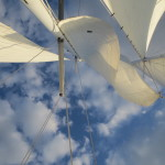 Looking up through the sails of the schooner to blue skies with white clouds