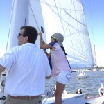 Young person hoisting the sails