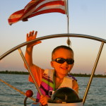 Young man peeking through the wheel at the helm and waving