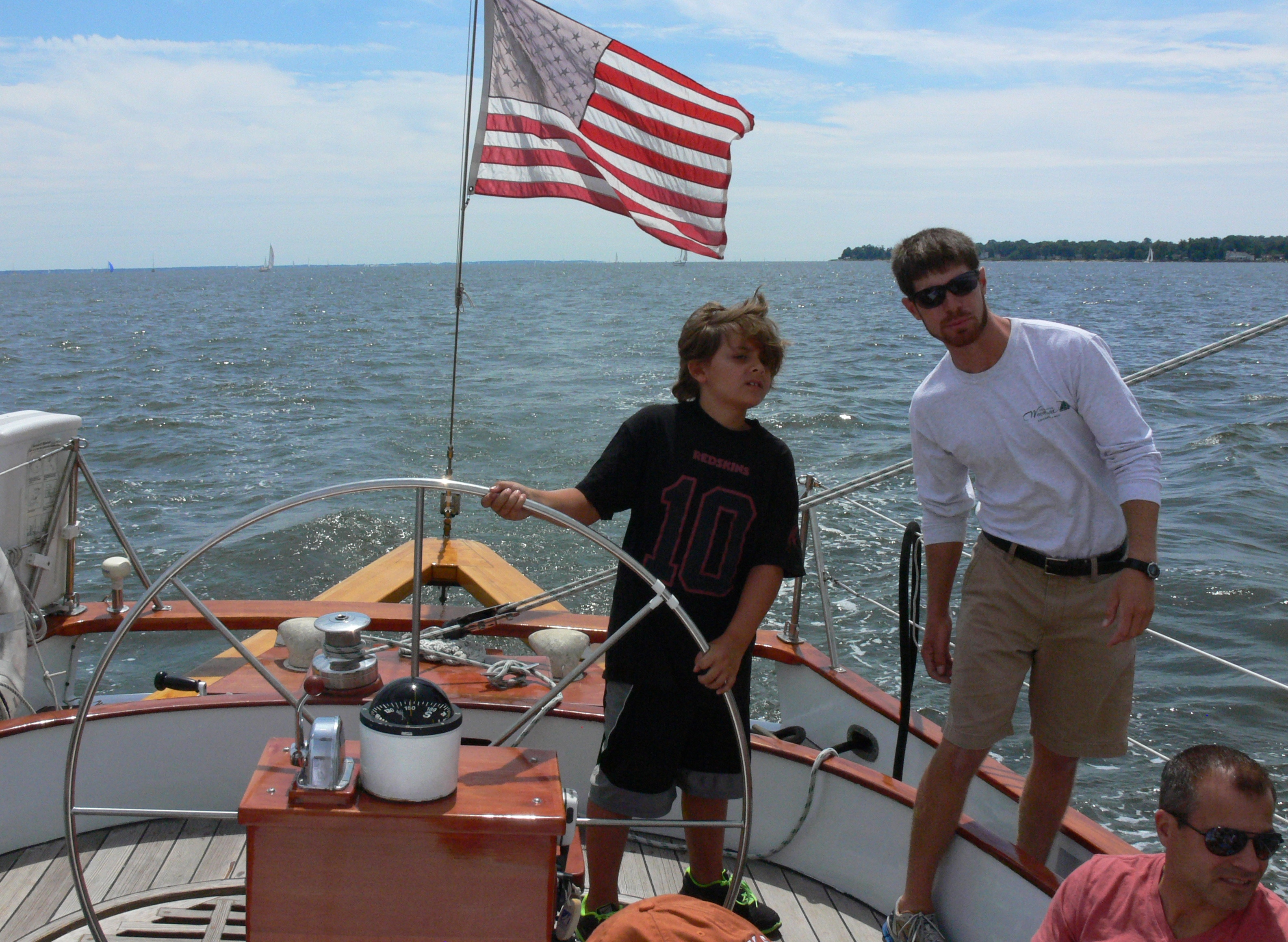 Young man steering the schooner as the captain looks on