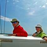 Couple one is in red jacket and one is in green jacket with beverage enjoying a sail