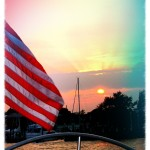 Amazing sunset with rays reflecting up from clouds viewed over the helm of schooner