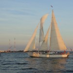 The sails of the schooner reflecting the sunset