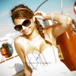 Beautiful young lady in a white dress sailing on the schooner