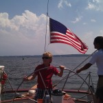 Boy steering the boat in a red shirt and blue and white shorts
