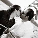 Couple in black and white photo kissing and steering the helm