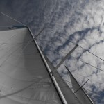 White sails going up into a blue sky with puffy clouds