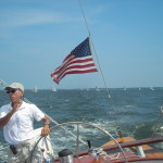The captain steering and talking to the guests on board the schooner