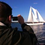 Man taking picture of schooner from other schooner on his phone