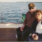 Couple smiling and enjoying a sunny sail