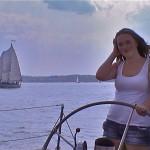 Women steering the boat with the other schooner over her shoulder