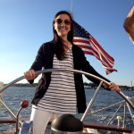 Women in striped navy and white top sailing the schooner with a smile