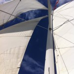 White sails against a blue sky with white clouds