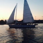 Calm waters reflecting sunset sail