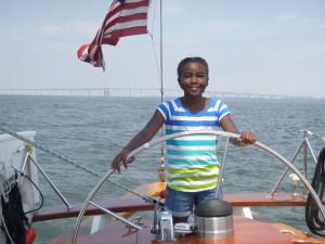 Nia at the wheel of the Schooner Woodwind II