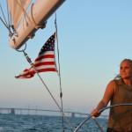 Women steering the schooner and looking into sunset