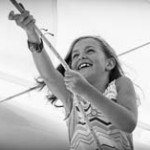 Black and white photo of little girl helping to raise the sails