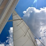 Sails, white clouds and blue skies