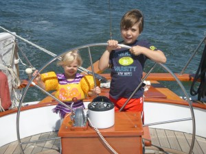 Wyatt and Caroline on the helm of the Schooner Woodwind