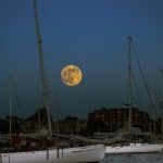 Huge ful moon over the moored sailboats in harbor