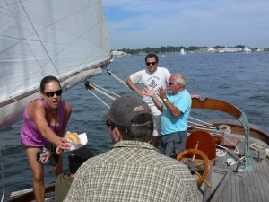 Captain Mark in light blue shirt, with Lisa feeding hungry James, while Ian watches patiently.