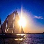 Brilliant blue sky and yellow sun behind the schooner while sailing