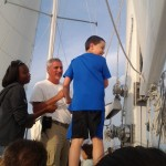 Young man laughing and helping with sails