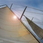 Looking straight up the sails at a sunny blue sky