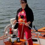 Women in pink with dark cap on sailing the schooner