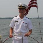 Man in USNA uniform steering the schooner